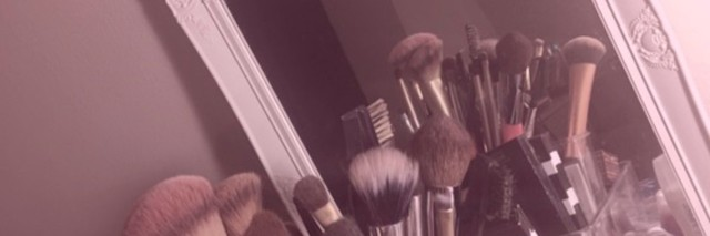 makeup supplies on dresser reflected in mirror