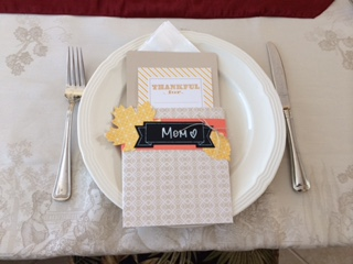 a place setting at a table with a card that says mom