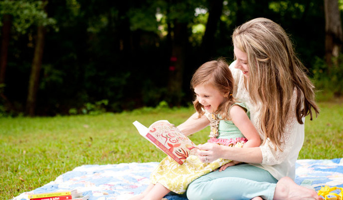 The author holding her daughter, reading a book together on a blanket in a park