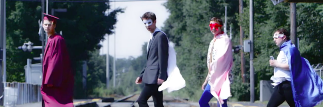 Members of Aspergers Are Us dressed in costumes walking along a railroad track