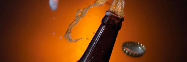beer bottle with beer spilling out