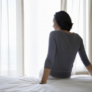 woman sitting on a white bed and looking out the window
