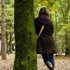 Woman wearing long coat, leaning against tree in park