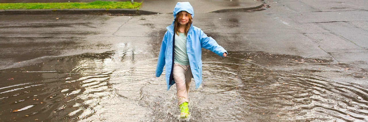 young girl playing in a rain puddle