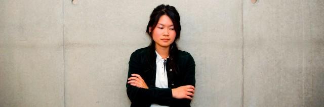 a woman sitting against a wall