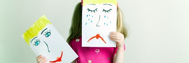 A little girl holding up a drawing of a sad face over her face