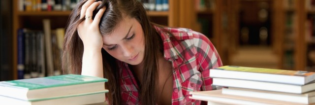 female student in plaid shirt studying in between piles of books at the library