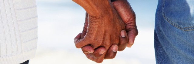man and woman holding hands at beach