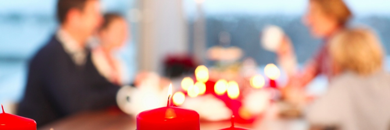 Close up of red candles with family in the background sitting at a table