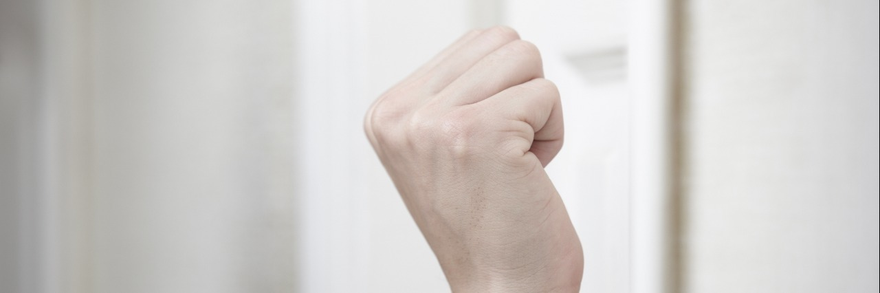 Human fist hovering in front of door, getting ready to knock