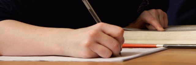 Student in classroom taking notes next to open book on table