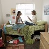 two young women sitting on a bed in their dorm room