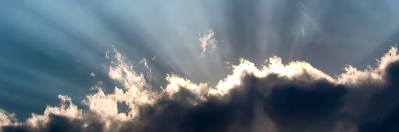 Crepuscular rays shining behind the cloud