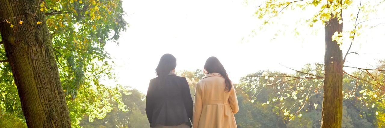Two women walking together in a park in the fall