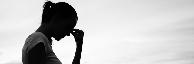 silhouette of sad woman with city skyline in background