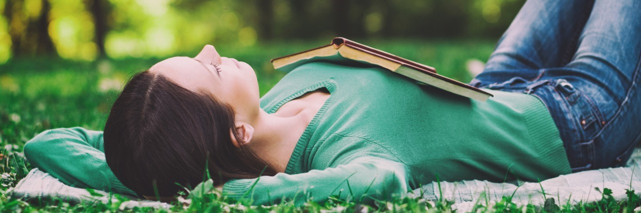 woman relaxing on her back in a grassy field with an open book on her chest
