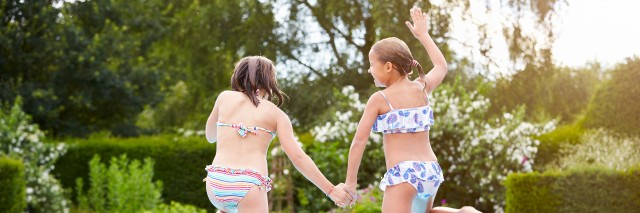 Two young girls jumping into swimming pool together.