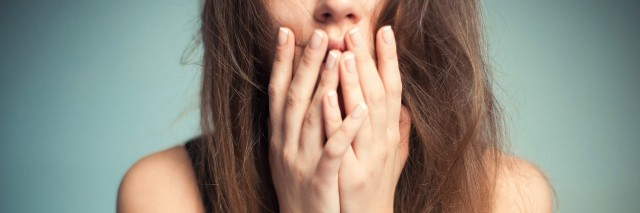 close up of woman covering her mouth with her fingers