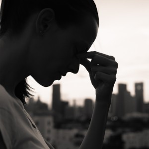 Black and white photo of woman in front of city landscape with eyes closed and fingers on the bridge of her nose