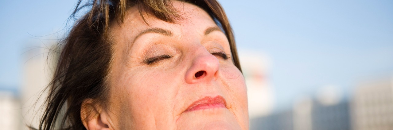 close up of older woman taking a deep breath