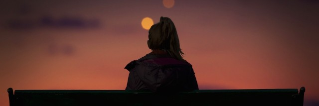 Silhouette of a girl watching city lights on a bench