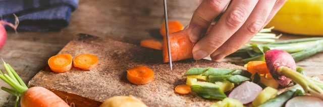 a woman chopping carrots in her kitchen