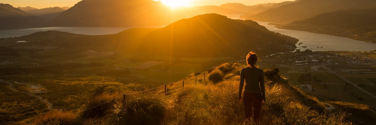 Woman silhouette at sunset on the mountain