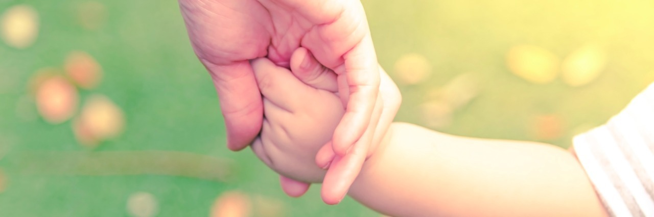 Parent holding baby's hand outdoors