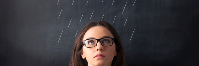 woman standing in front of chalkboard with rain clouds drawn above her head