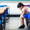 Student sitting at desk in classroom with head in hands