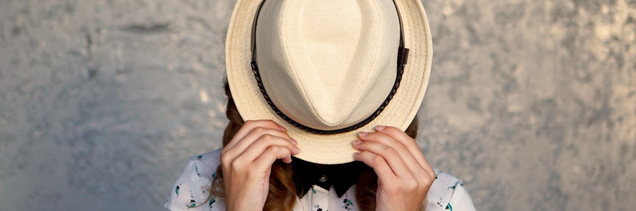 woman hiding face with hat