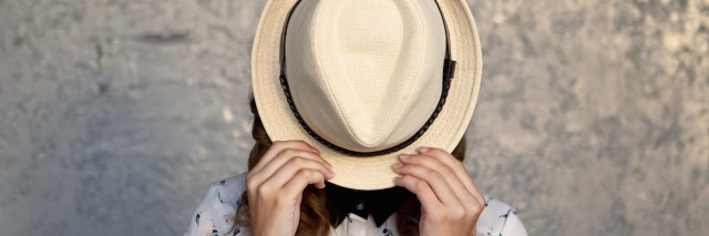 a woman hiding behind her hat