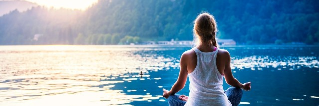 young woman meditating on a dock in front of a lake and mountains