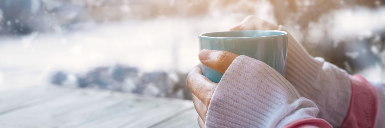 woman's hands holding warm cup of coffee outside in the snow