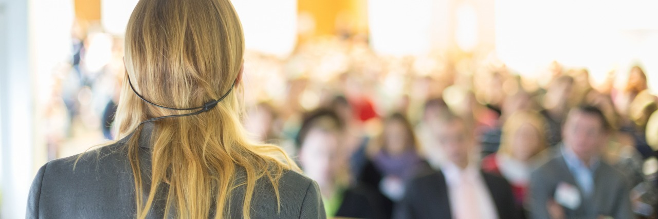 woman speaking into a microphone and leading a business conference