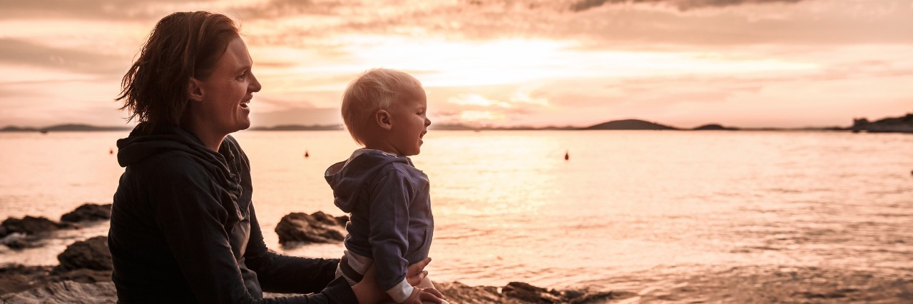 mother and son sitting on rocky ledge looking at a sunset over the ocean