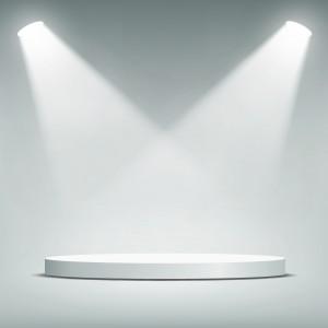 Round pedestal illuminated by spotlights.