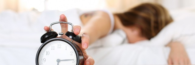 woman laying in bed with her face buried in her pillow reaching out to shut off her alarm clock