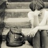 A woman sits on the concrete stairs in a very depressed mood, lying next to her on the stairs is her backpack.