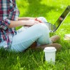 female student working on laptop while sitting in a park