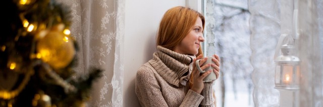 woman in brown sweater sits on a couch next to a christmas tree drinking tea and looking out a window at the snow