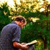 Guy reading book in the park