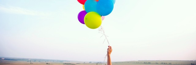 hand holding colorful balloons