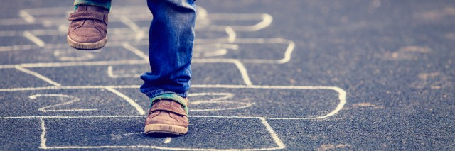Child playing hopscotch on playground outdoors.
