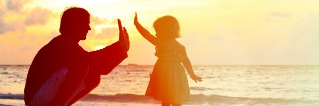 parent high fiving young daughter at the beach