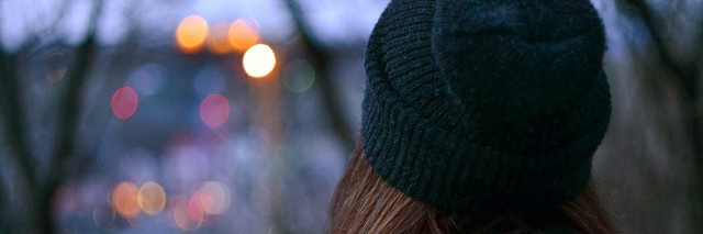 girl in winter clothing looking towards city lights