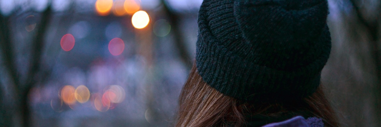 Woman wearing beanie, looking at city lights through tree branches