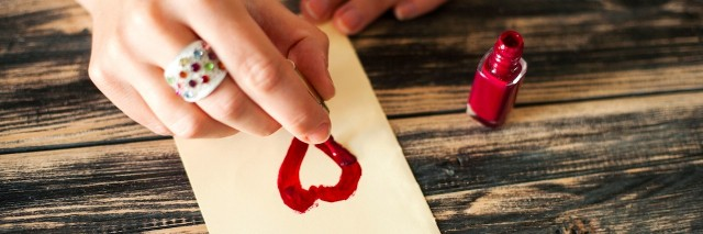 A woman painting a heart on a piece of paper