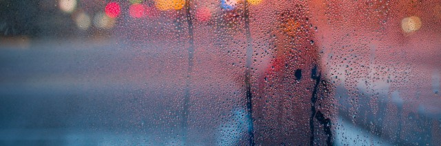 image of a woman in the rain through a glass window