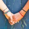 close up on two women holding hands in front of wooden background